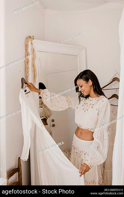 Bride holding wedding dress while standing at home