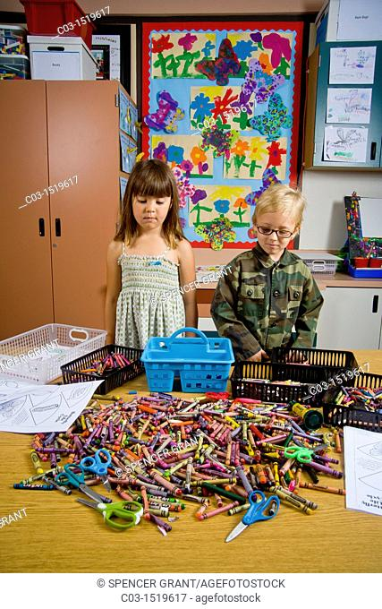 Kindergarten children in San Clemente, CA, contemplate a table full of classroom objects including crayons and worksheets