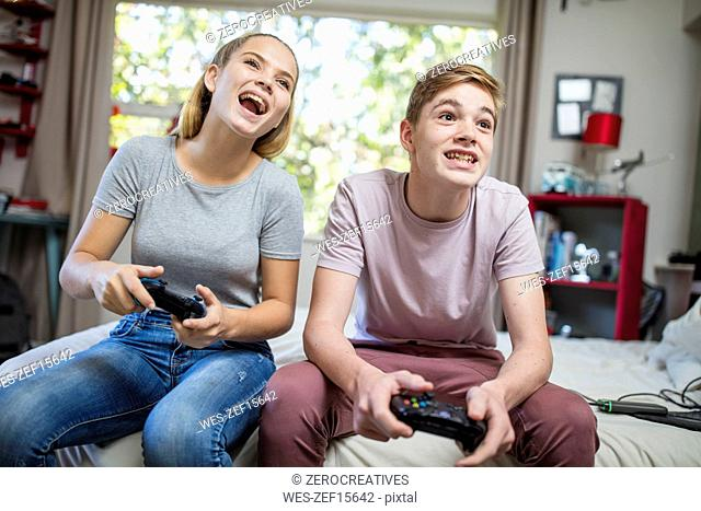 Happy teenage girl and boy sitting on bed playing video game