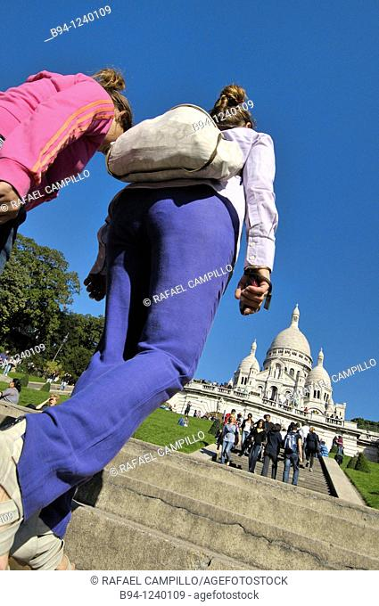 People climbing stairs in front of the Basilica Sacré-Coeur. Montmartre. Paris, France