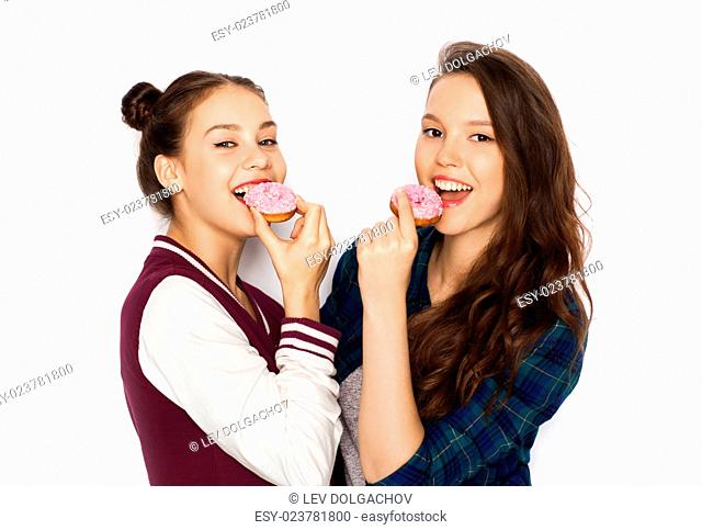 people, friends, teens and friendship concept - happy smiling pretty teenage girls with donuts eating and having fun