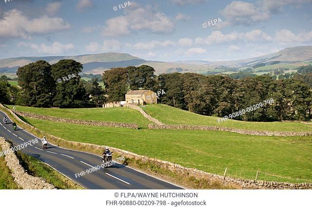 Motorcyclists on rural road speeding and doing wheelie, Hawes, Wensleydale, Yorkshire Dales N.P., North Yorkshire, England, September