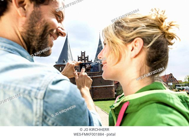 Germany, Luebeck, couple taking picture in front of the Holsten Gate