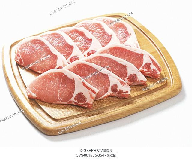 Uncooked Pork Chops on Cutting Board