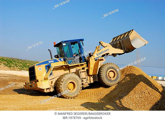 Wheel loader at a construction site rearranging gravel, crushed stone and antifreeze