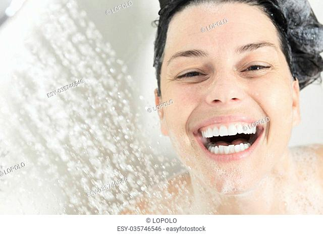 A Happy smiling woman washing shoulder showering in bathroom
