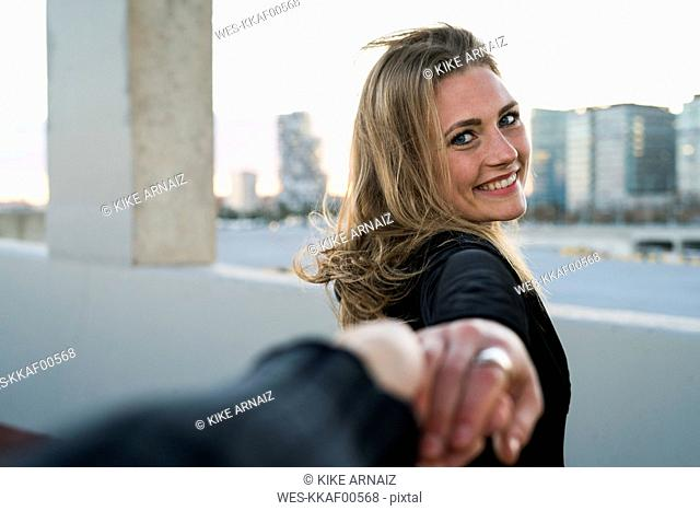 Spain, Barcelona, portrait of happy young woman holding hand