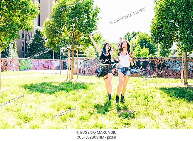 Two young women laughing and running in urban park