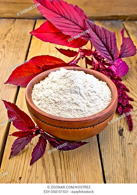 Amaranth flour in a clay bowl and purple amaranth flower on the background of wooden boards