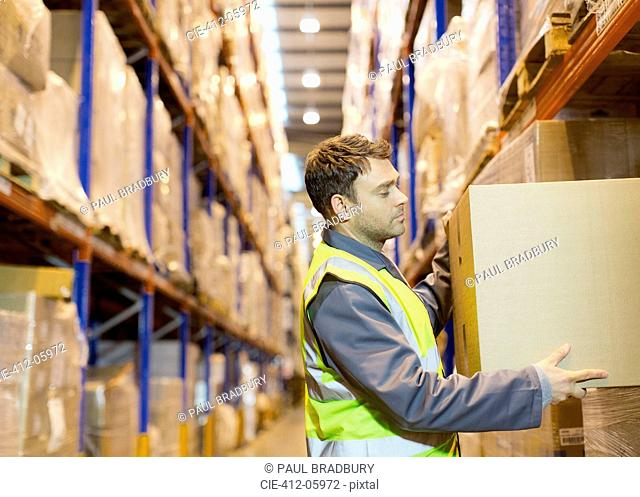 Worker stacking boxes in warehouse