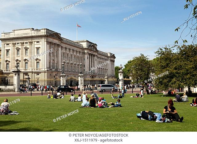 Tourists resting on the grass outside Buckingham Palace