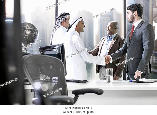 Western businessmen having meeting in Middle Eastern office