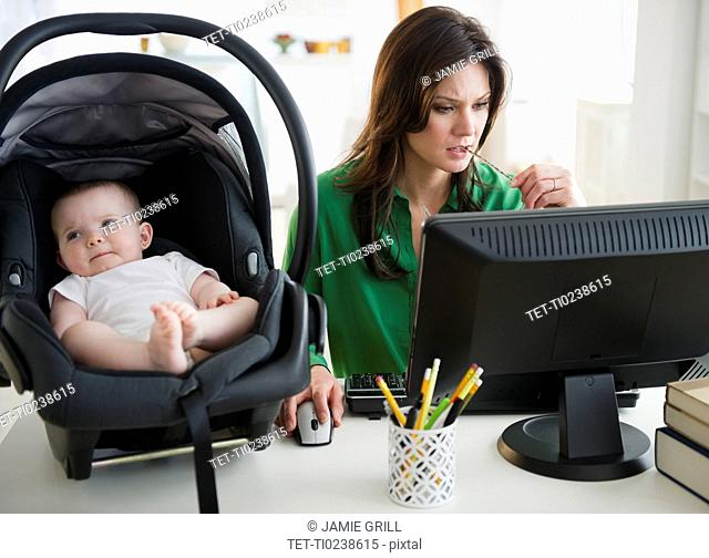 Mother working on computer, baby daughter 6-11 months on desk