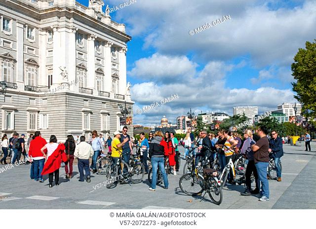 Group of tourists with bicycles next to the Royal Palace. Bailen street, Madrid, Spain