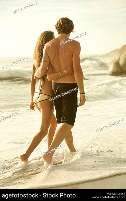 Couple embracing each other while walking in water at beach
