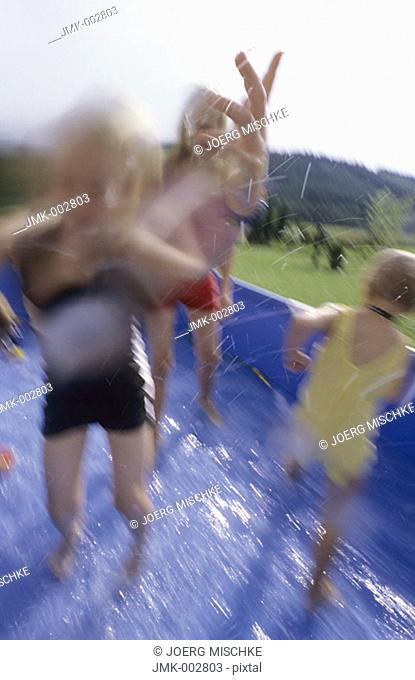 Three children, girls, 5-10 years old, playing in the garden in a swimming pool