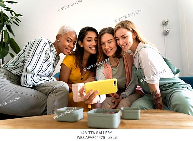 Four women sitting on couch taking a selfie