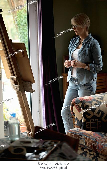 Female artist observing painting on canvas