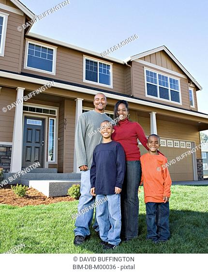 African family posing in front of house