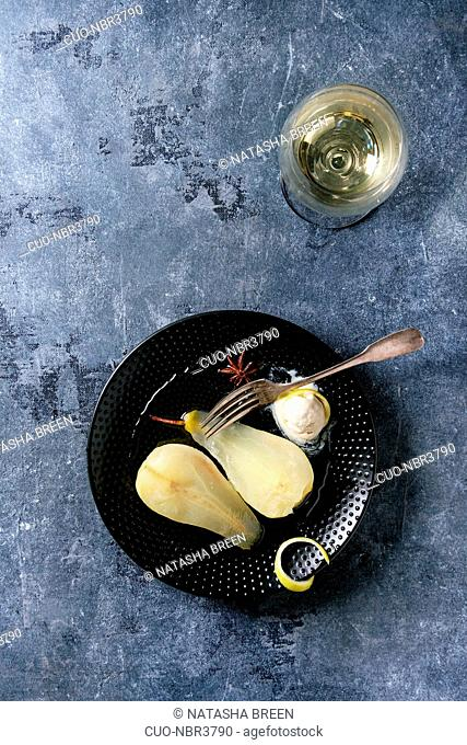 Traditional dessert sliced poached pears in white wine served in black plate with syrup, ice cream, lemon zest and glass of white wine over blue texture...