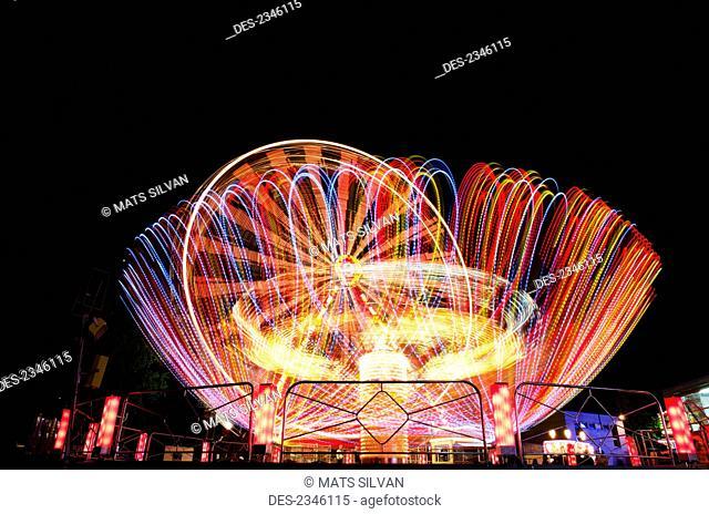 Colourful lights blurring on amusement park rides at night; Locarno, Ticino, Switzerland