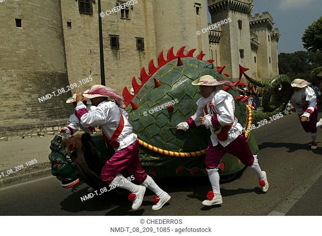 Four people pushing a wooden dragon, Provence, France
