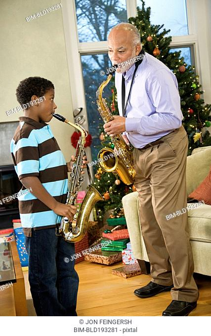 African American grandfather playing saxophone with grandson