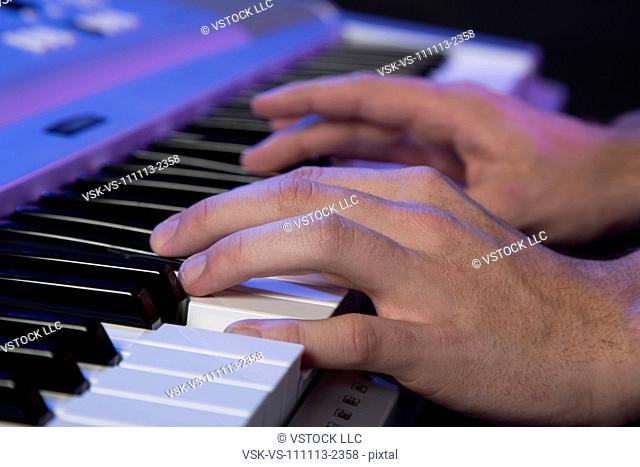 Hands of male musician playing keyboard