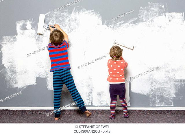 Rear view of female toddler and brother painting wall