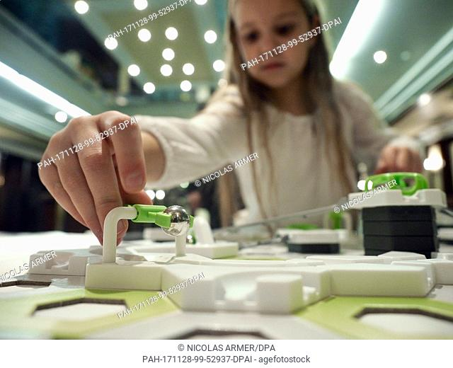 A girl playing with a ball track system by Ravensburger, which works with magnetism, in Nuremberg, Germany, 28 November 2017