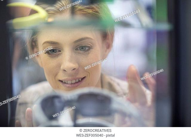 Young woman looking through shop window