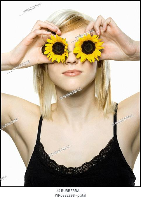 Close-up of a young woman holding sunflowers in front of her eyes