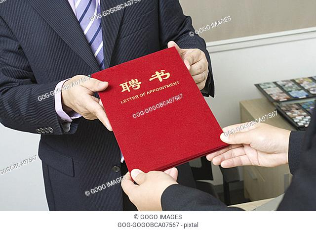 "Businessman handing colleague a ""Letter of Appointment"""