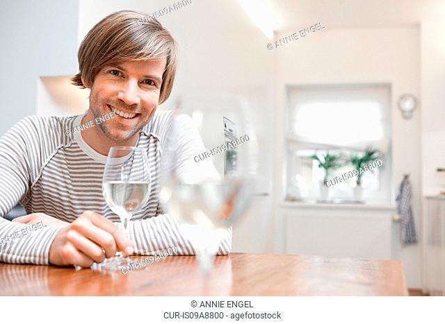 Man with white wine in kitchen