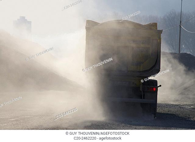 Lorry, truck transporting stones, with red brake light, through dust, France