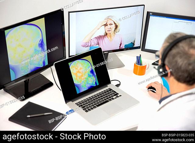 A GP during a video consultation with a 45-year old woman for head pain. An x-ray of her brain can be seen on the screen