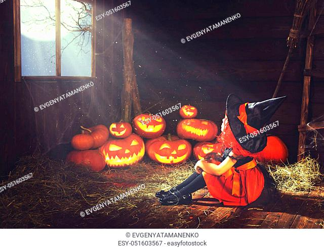 Halloween. child little witch with pumpkin by the window waiting for a miracle and magic in old hut