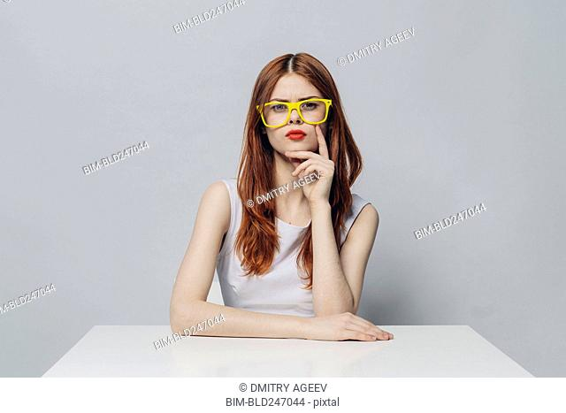 Serious Caucasian woman sitting at table wearing yellow eyeglasses