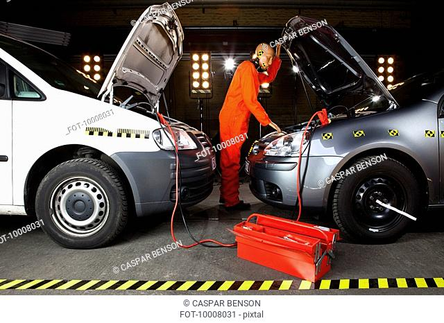 A crash test dummy using jumper cables with two cars