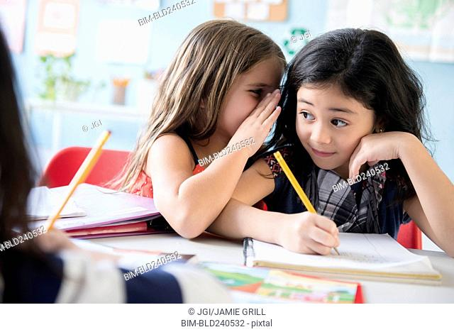 Girl whispering to classmate in school