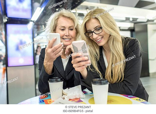 Two mature female friends looking at smartphones in shopping mall cafe