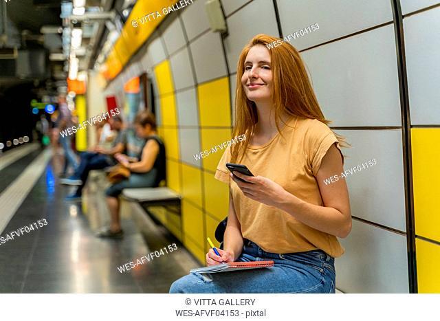 Woman using smartphone in underground station