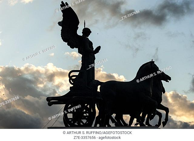 Silhouette of Statue of Goddess Victoria on a Quadriga (Winged Victory Statue) at sunset. Victor Emmanuel II Monument (Monumento Nazionale a Vittorio Emanuele...