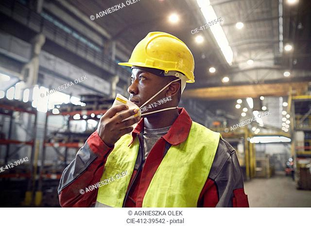 Steelworker removing protective mask in steel mill