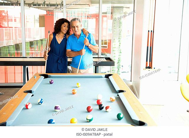 Senior man and wife at pool table