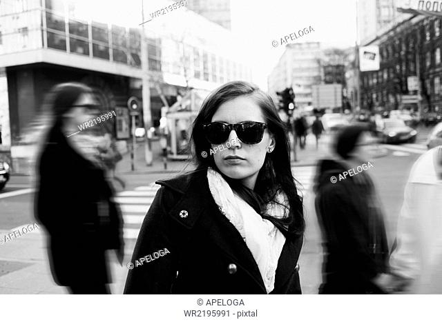 Confident young woman in sunglasses standing on city street