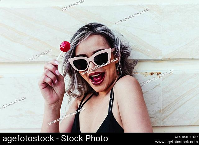 Happy attractive woman holding lollipop against wall
