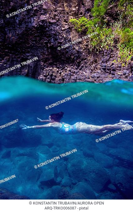 Young woman diving underwater