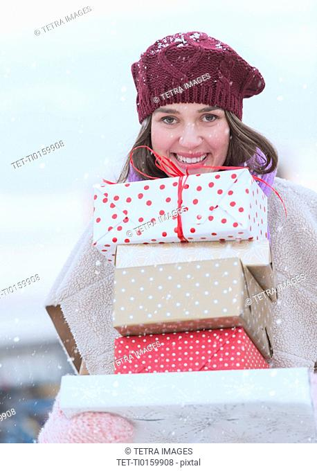 Portrait of young woman carrying stack of Christmas presents