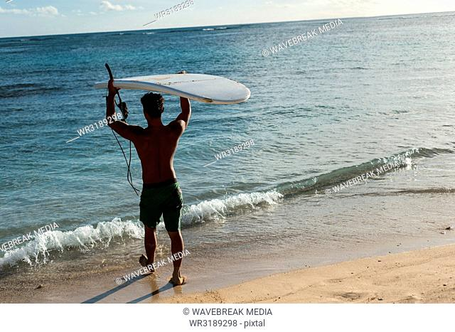 Male surfer walking with surfboard in the beach